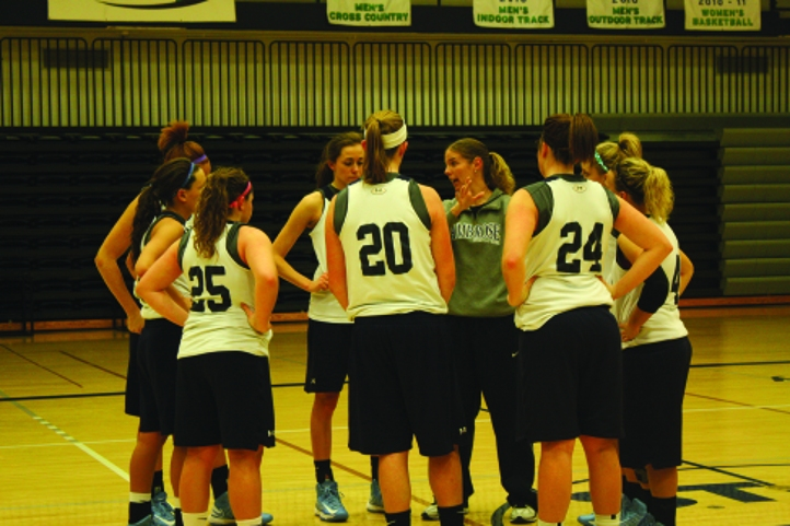 The Queen Bees huddle at practice to discuss their offensive plays. Photo by Mary Schechinger.
