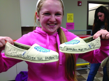 Freshman Jessica Gascho shows off the TOMS she decorated at the Style Your Sole event. The Buzz/Submitted.