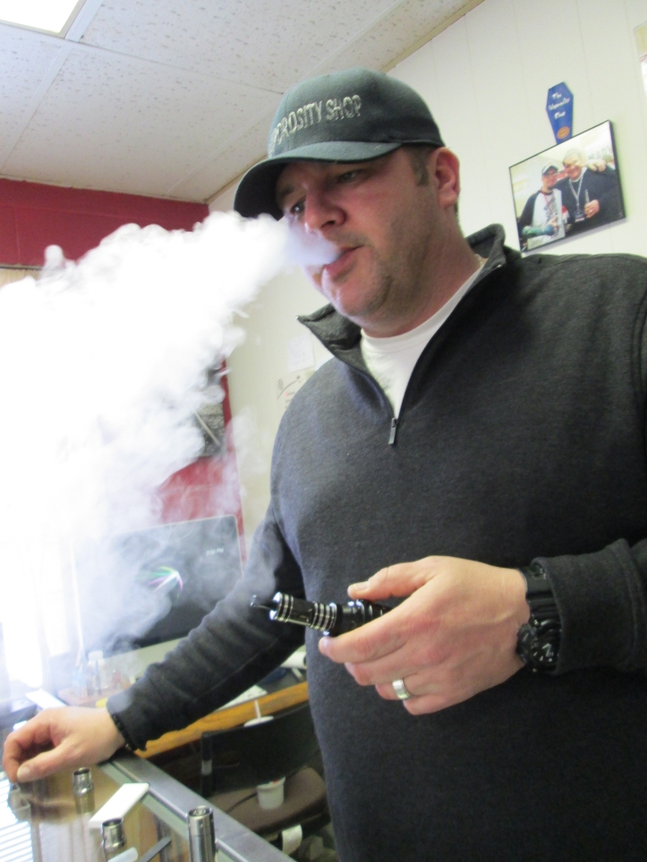 Todd Smith, owner of the Vaporosity Shop, demonstrates vaping with an e-cigarette. Smith opened his store in 2012. Tyler Mitchell/The Buzz.